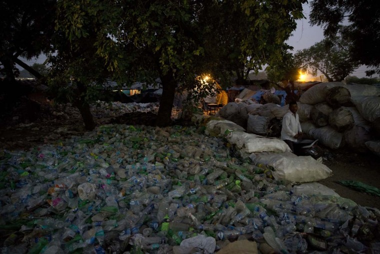 An Indian garbage collector sits beside heaps of plastic bottles on World Environment Day in Allahabad, India, Monday, June 5,2017. (AP Photo/Rajesh Kumar Singh)