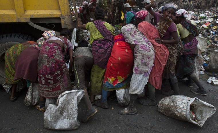 Indian ragpicker women throng to collect recyclable materials as a truck prepares unloads garbage at a dumping site on the outskirts of Gauhati, Assam state, India, Monday, June 5, 2017. Monday marks World Environment Day. (AP Photo/Anupam Nath)