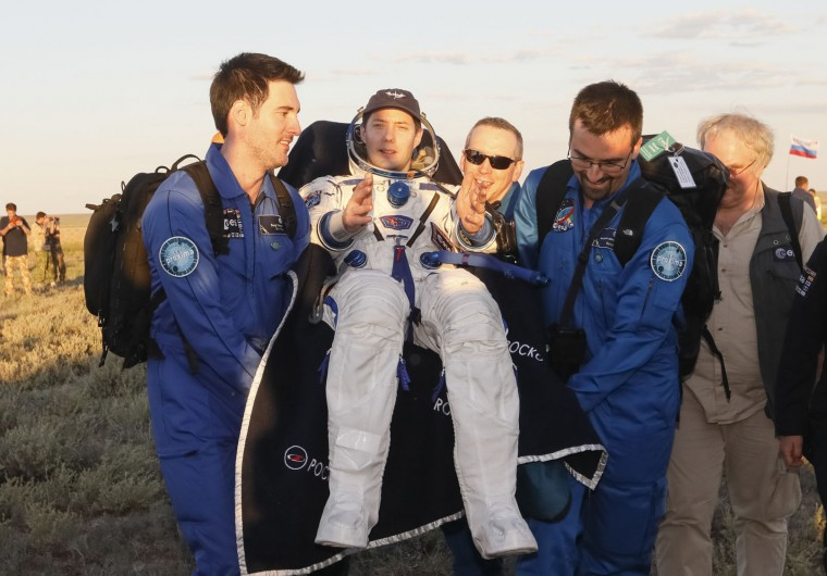 Ground personnel carry International Space Station crew member, French astronaut Thomas Pesquet, after landing in a remote area outside the town of Dzhezkazgan, Kazakhstan, Friday, June 2, 2017. The capsule with Russian cosmonaut Oleg Novitsky and French astronaut Thomas Pesquet, landed Friday on the steppes of Kazakhstan. (Shamil Zhumatov/Pool Photo via AP)