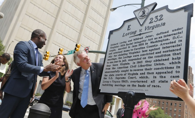 Virginia Gov. Terry McAuliffe , right, looks over a historical marker, along with his wife, Dorothy, center, and Richmond Mayor Lavar Stoney, left, that was unveiled commemorating the 50th anniversary of the U.S. Supreme Court decision that struck down bans on interracial marriage Monday, June 12, 2017, in Richmond, Va. The new historical marker to commemorate the lawsuit brought by Richard and Mildred Loving, was dedicated outside the old Virginia Supreme Court, which ruled against the Lovings before they ultimately won in the U.S. Supreme Court. (AP Photo/Steve Helber)
