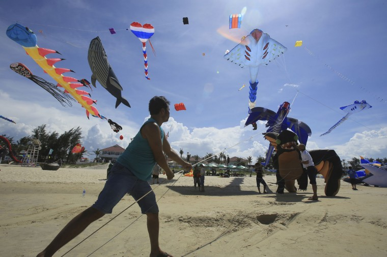 In this Sunday, June 11, 2017, photo, a flyer controls the string of kites on Tam Thanh beach during an International Kite Festival in Quang Nam province, Vietnam. Hundreds of flying giant sea creatures, animal shaped and folklore inspired kites from 20 countries were taken to the sky. (AP Photo/Hau Dinh)