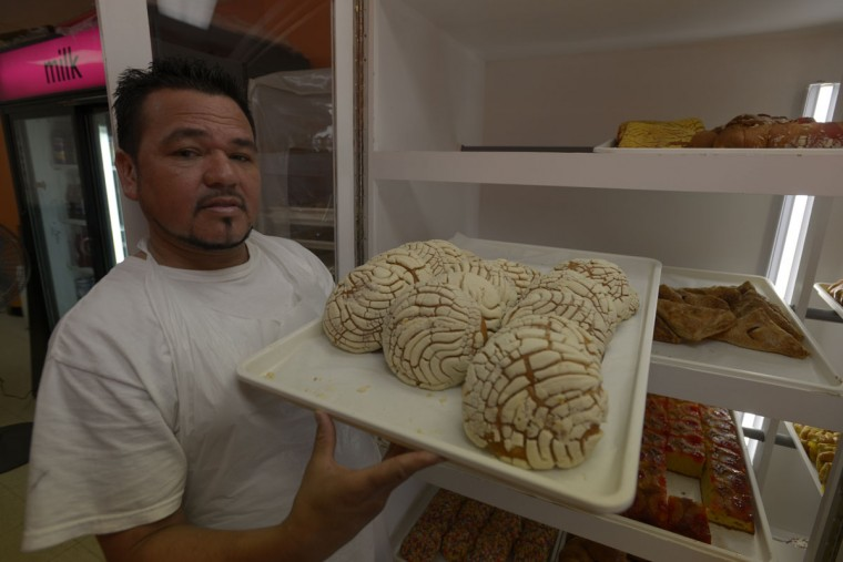 "Alberto Lesner with a sheet of conchas, a type of Latin American sweet bread, which he sells at his shop on Eastern Avenue in Highlandtown. The shop, one of several Latin ""panaderias"" in the neighborhood, sells a variety of El Salvadoran and Mexican treats. (Christina Tkacik/Baltimore Sun)"