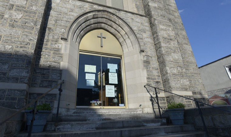 Signs on Nazareth Lutheran Church on Bank Street and Highland Avenue advertise English classes and mass in Spanish to members of the Latin community. (Christina Tkacik/Baltimore Sun)