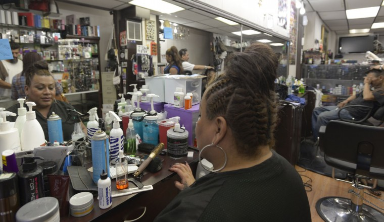 A stylist takes a break at Castillo & Villegas, one of the many salons in Highlandtown. (Christina Tkacik/Baltimore Sun)