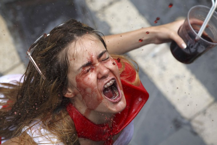 A reveller catches wine thrown from a balcony during the opening day or 'Chupinazo' of the San Fermin Running of the Bulls fiesta on July 6, 2017 in Pamplona, Spain. The annual Fiesta de San Fermin, made famous by the 1926 novel of US writer Ernest Hemingway entitled 'The Sun Also Rises', involves the daily running of the bulls through the historic heart of Pamplona to the bull ring. (Photo by Pablo Blazquez Dominguez/Getty Images)