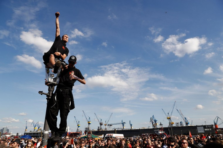 "Protesters listen to live music during the ""Welcome to Hell"" rally against the G20 summit in Hamburg, northern Germany on July 6, 2017. Leaders of the world's top economies will gather from July 7 to 8, 2017 in Germany for likely the stormiest G20 summit in years, with disagreements ranging from wars to climate change and global trade. / (AFP Photo/Odd Andersen)"