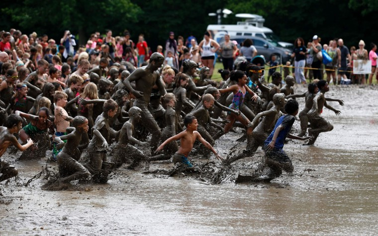 Children race in the pit at Wayne County's annual Mud Day at Nankin Mills Park on July 11, 2017 in Westland, Michigan. The mud pit contains 200 tons (181 metric tons) of top soil and 20,000 gallons (75,708 liters) of water. (Jeff Kowalsky/AFP/Getty Images)