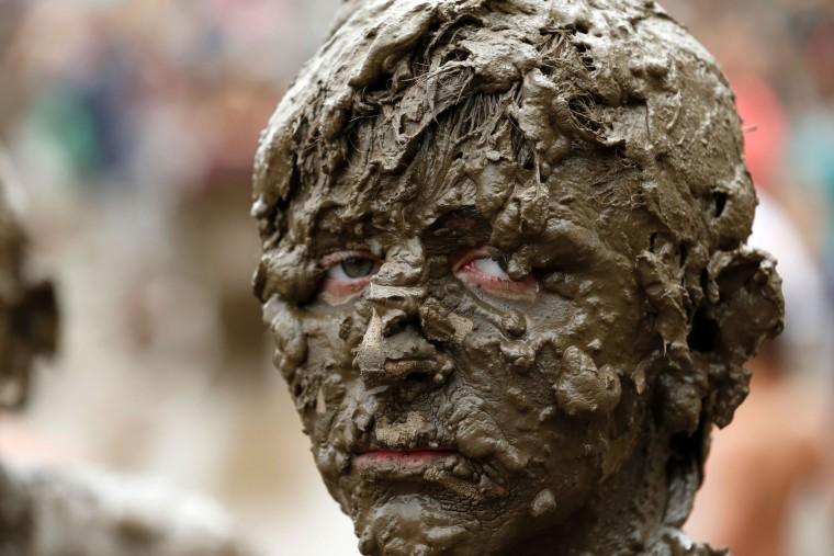 Brendan Weening of Ypsilanti, Michigan plays in the pit at Wayne County's annual Mud Day at Nankin Mills Park on July 11, 2017 in Westland, Michigan. The mud pit contains 200 tons (181 metric tons) of top soil and 20,000 gallons (75,708 liters) of water. (Jeff Kowalsky/AFP/Getty Images)
