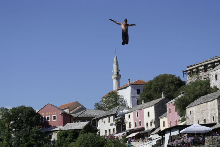 Spectators watch as a diver jumps from the Old Mostar Bridge during 451th traditional annual high diving competition, in Mostar, 140 kms south of Bosnian capital of Sarajevo, Sunday, July 30, 2017. Total of 41 divers from Bosnia and neighbouring countries competed diving from 25 meters high Old Mostar Bridge into the Neretva river. (AP Photo/Amel Emric)