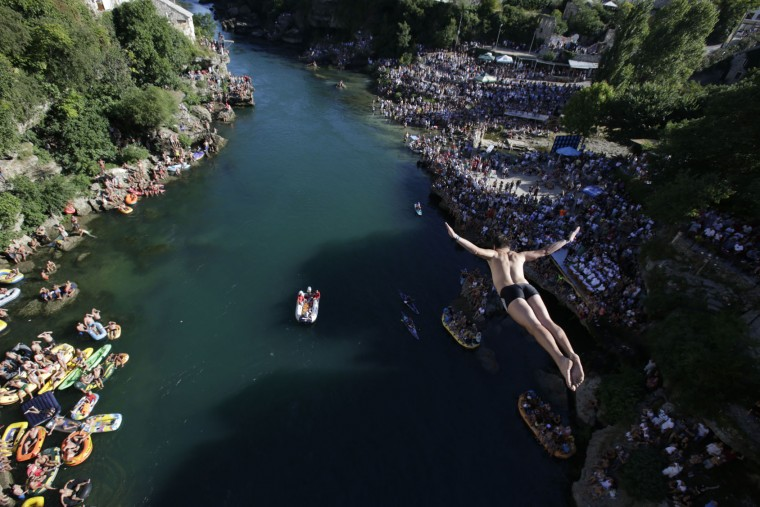 A diver drops through the air from the Mostar bridge during the 451th traditional annual high diving competition, in Mostar, 140 kms south of Bosnian capital of Sarajevo, Sunday, July 30, 2017. Total of 41 divers from Bosnia and neighbouring countries competed diving from 25 meters high Old Mostar Bridge into the Neretva river. (AP Photo/Amel Emric)