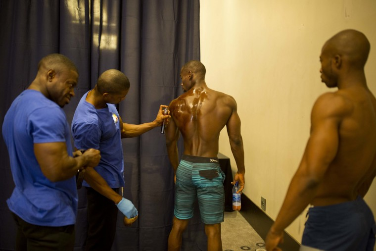 In this July 23, 2017 photo, Raynold Junior Mendez gets help with his body oil before competing in a bodybuilding event between Haiti and Dominican Republic in Port-au-Prince, Haiti. Sunday's event was organized by the Dominican bodybuilding federation and a local Haitian bodybuilding group to generate support for the sport and make it more accessible, especially in Haiti where a handful of bodybuilders struggle to become professionals in a country where people make less than $2 a day. (AP Photo/Dieu Nalio Chery)