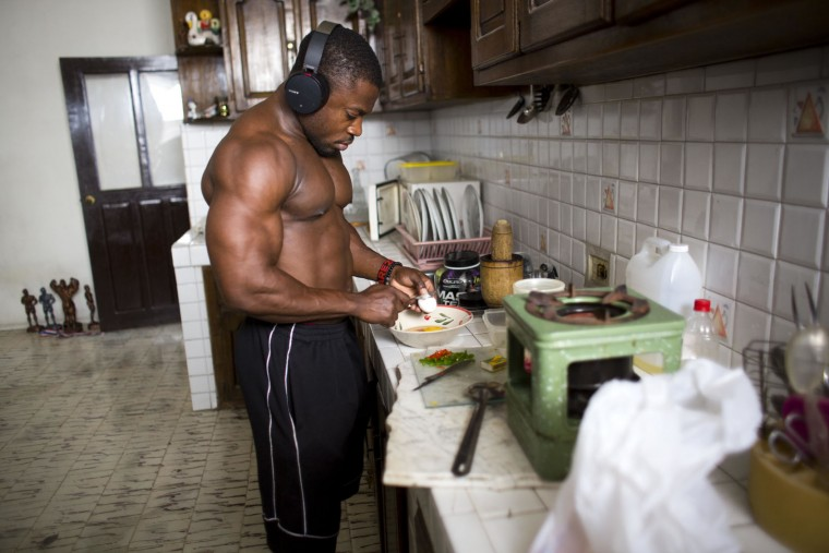 "In this July 21, 2017 photo, Haitian bodybuilder Spely Laventure prepares a special breakfast at his home in Port-au-Prince, Haiti. Laventure spends anywhere between $50 to $100 a week on a single meal plan, considered an exorbitant amount in the poorest country in the Western Hemisphere. ""I was a skinny guy, but look at me right now,"" said the 30-year-old who won five competitions in the past year. (AP Photo/Dieu Nalio Chery)"