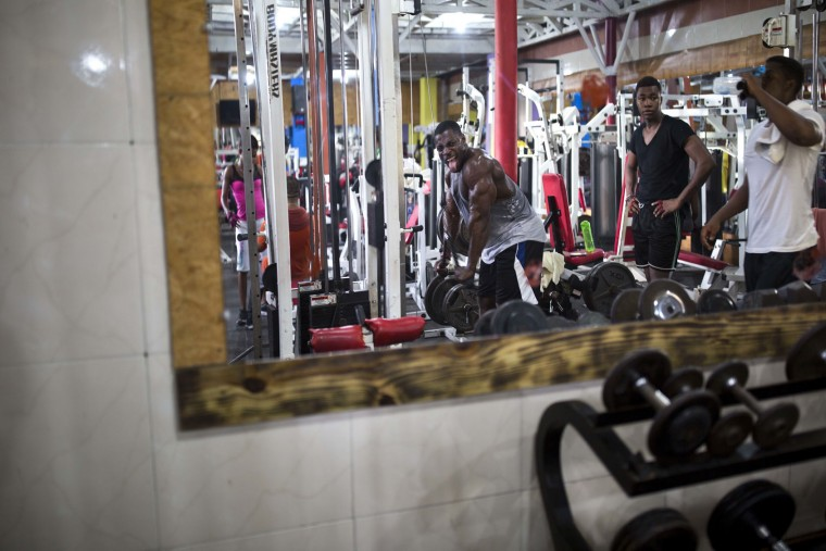 In this July 20, 2017 photo, Haitian bodybuilder Spely Laventure makes a face in the mirror as he trains for an upcoming competition in Port-au-Prince, Haiti. Laventure gets to work out for free thanks to the owner of the local gym in Haiti's capital. (AP Photo/Dieu Nalio Chery)