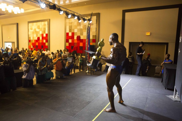 "In this July 23, 2017 photo, Haitian bodybuilder Spely Laventure holds his trophy up as photographers take his picture after winning the first bodybuilding competition between Haiti and Dominican Republic in Port-au-Prince, Haiti. ""I proved everyone that I'm really a champion,"" he said. Laventure won his weight category as well as the overall show. (AP Photo/Dieu Nalio Chery)"