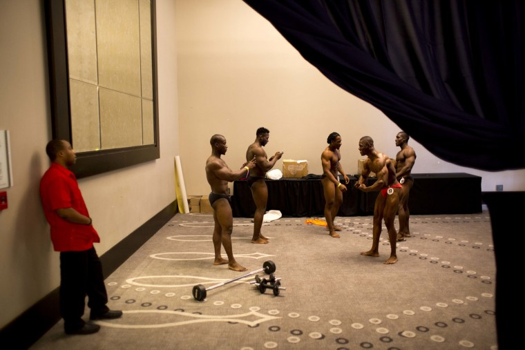 In this July 23, 2017 photo, Haitian bodybuilders take pictures before the start of a bodybuilding competition between Haiti and Dominican Republic in Port-au-Prince, Haiti. Bodybuilders from Haiti and the Dominican Republic flexed and strutted against each other on stage in the first such showdown between the neighboring countries whose relations are often tense. (AP Photo/Dieu Nalio Chery)