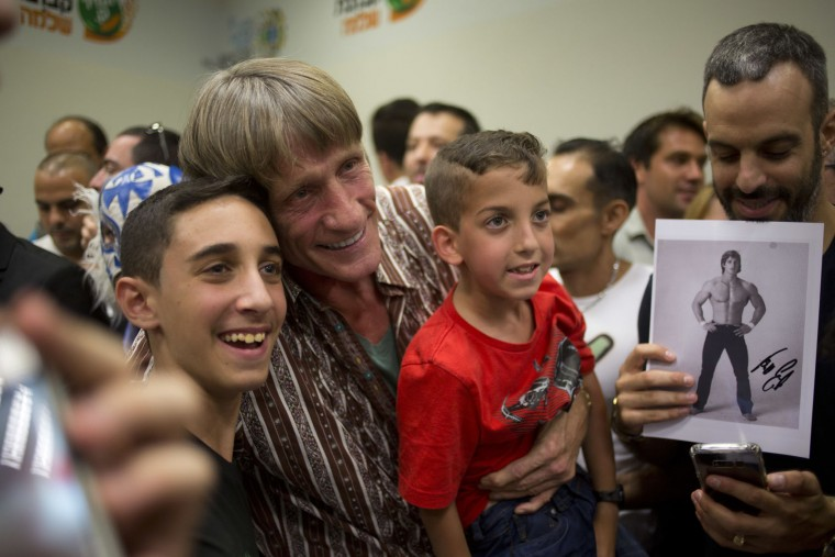 Wrestler Kevin Von Erich poses with fans ahead of The Rage Wrestling Mega Show in Tel Aviv, Israel, Sunday, July 9, 2017. The Israeli Wrestling League hosted a wrestling show in Tel Aviv with some of the WWE greatest of all time. (AP Photo/Ariel Schalit)