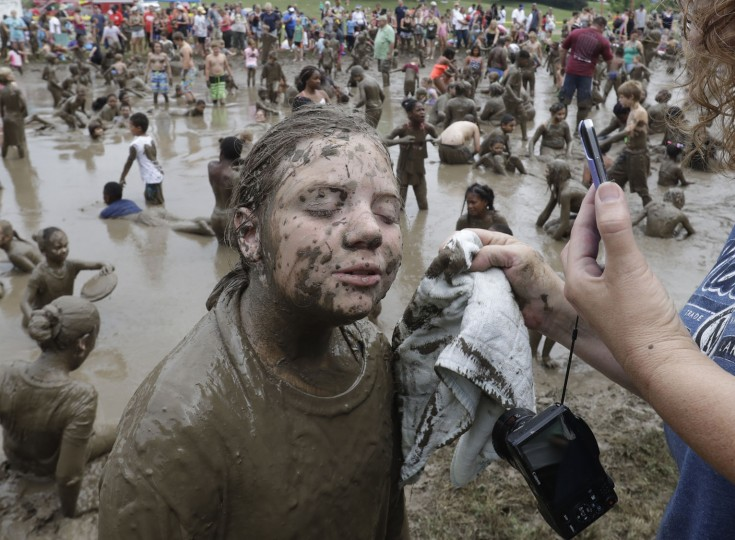 Haylie Sapp, 10, has her face wiped during Mud Day at the Nankin Mills Park, Tuesday, July 11, 2017 in Westland, Mich. The annual day sponsored by the Wayne County Parks takes place in a 75' x 150' giant mud pit that gives children the opportunity to get down and dirty at one of the messiest playgrounds Southeast Michigan has ever seen. (AP Photo/Carlos Osorio)