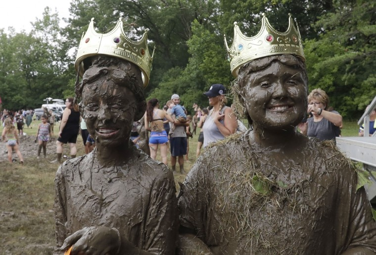 Mackenna Kofahl, 10, left, and Brian Wilson, 10, poses after being named 2017 Queen and King of the annual Mud Day at the Nankin Mills Park, Tuesday, July 11, 2017, in Westland, Mich. The annual day sponsored by the Wayne County Parks takes place in a 75 foot by 150 foot giant mud pit that gives children the opportunity to get down and dirty at one of the messiest playgrounds Southeast Michigan has ever seen. (AP Photo/Carlos Osorio)