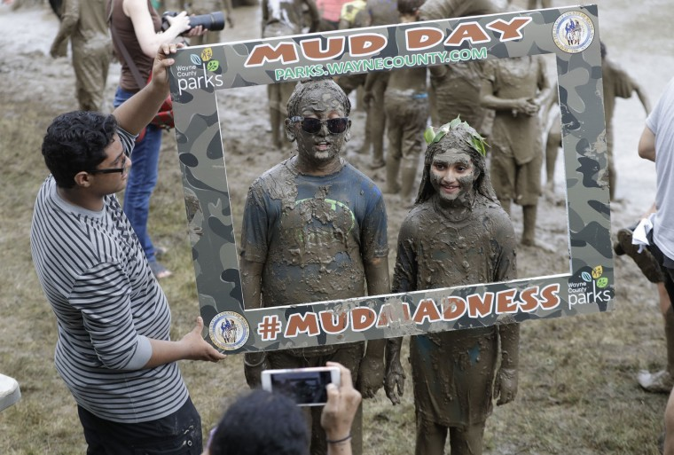Kids pose for a photo during Mud Day at the Nankin Mills Park, Tuesday, July 11, 2017 in Westland, Mich. The annual day sponsored by the Wayne County Parks takes place in a 75' x 150' giant mud pit that gives children the opportunity to get down and dirty at one of the messiest playgrounds Southeast Michigan has ever seen. (AP Photo/Carlos Osorio)