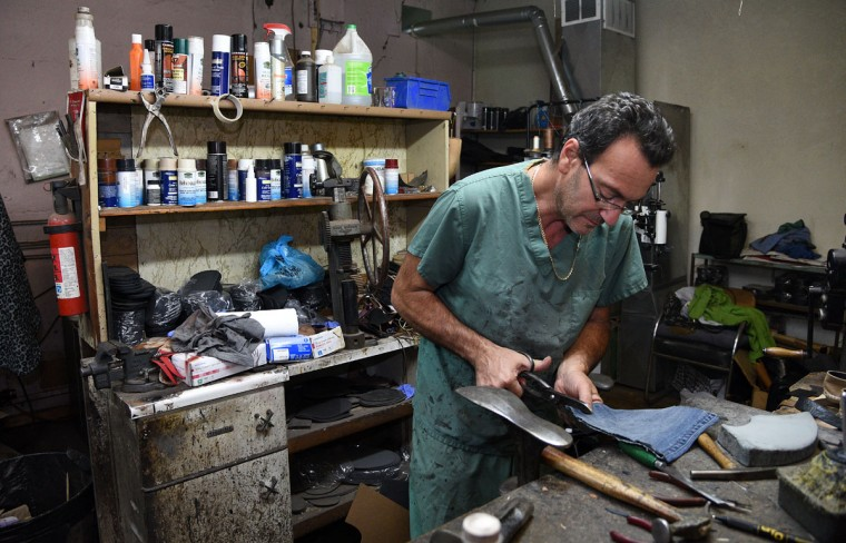 Eugene Gomberg cuts a piece of denim fabric for a pocket that he'll sew onto an animal carrier at the request of one of his customers. He is owner of ESG Shoe Repair in Roland Park and has been a cobbler for 25 years. He has been awarded Baltimore's Best cobbler many times over the years. (Barbara Haddock Taylor/ Baltimore Sun)