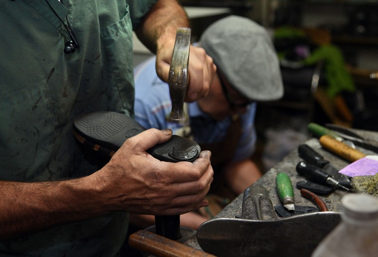Eugene Gomberg uses a shoe hammer to nail a heel guard onto a shoe in his shop. (Barbara Haddock Taylor/ Baltimore Sun)