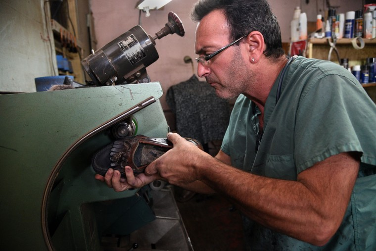 Eugene Gomberg uses a machine called a finisher on a shoe in his shop. (Barbara Haddock Taylor/ Baltimore Sun)