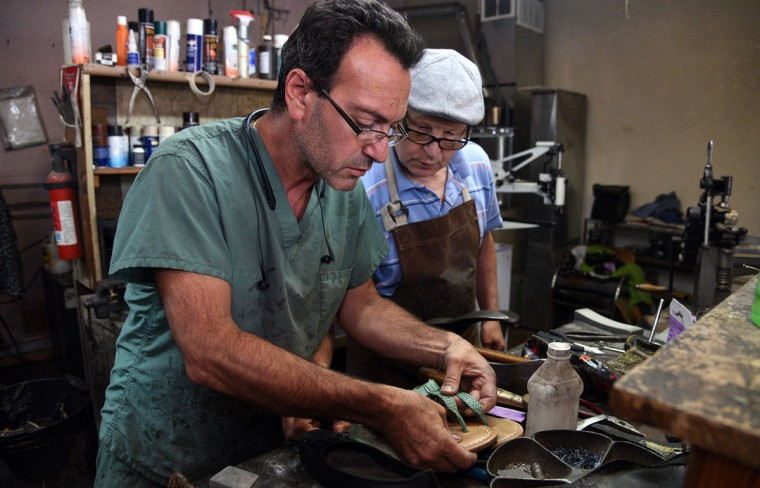 Eugene Gomberg, left, and helper Leonid Boryachinsky, right, look at a pair of sandals that need to be repaired. Mr. Gomberg is owner of ESG Shoe Repair in Roland Park. and has been a cobbler for 25 years. Mr. Boryachinsky, a friend, helps out when things get busy. (Barbara Haddock Taylor/ Baltimore Sun)