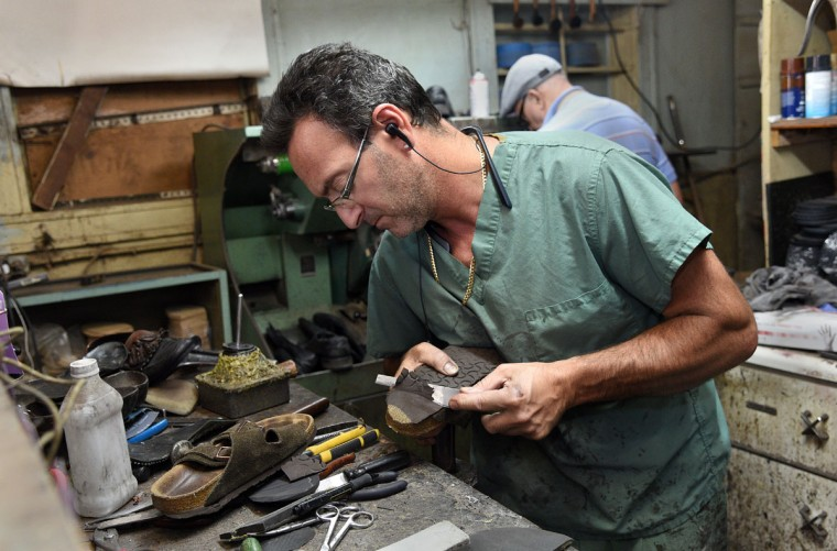 Eugene Gomberg, owner of ESG Shoe Repair in Roland Park, uses a knife to remove the sole of a Birkenstock sandal. He has been a cobbler for 25 years and has been awarded Baltimore's Best cobbler many times. (Barbara Haddock Taylor/ Baltimore Sun)