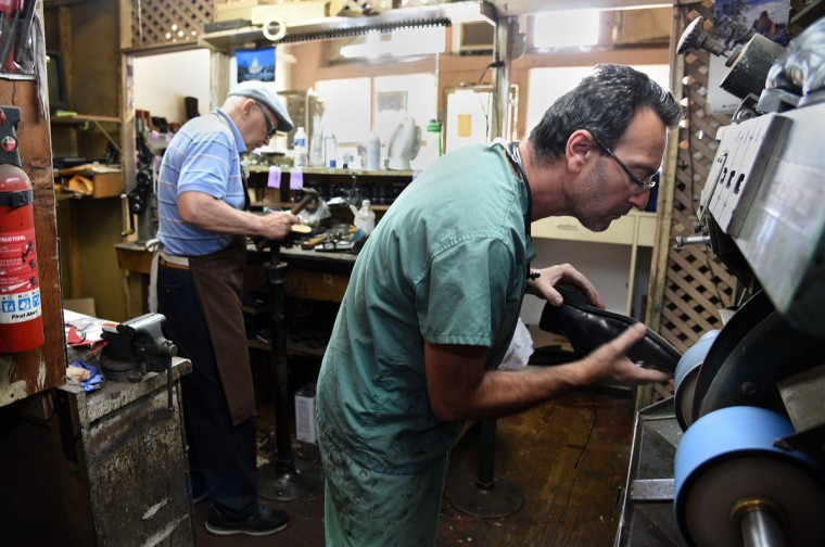 Eugene Gomberg, right, uses a machine called a finisher on a shoe in his shop. (Barbara Haddock Taylor/ Baltimore Sun)