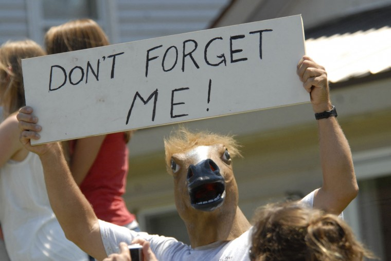 A man holds a sign asking to be rounded up with the Wild Chincoteague Pony herd while wearing a horse mask on the parade route following the 86th annual Chincoteague Pony Swim on Wednesday, July 27, 2011. Photo by Jay Diem/Daily Times)