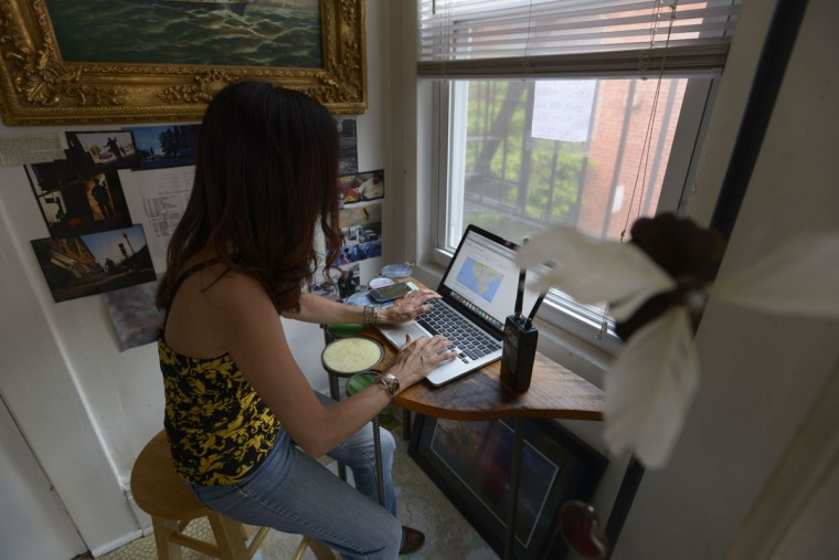 Friends generally don't expect Maggie Ybarra to hang out on weekends: that's her time to roam the city, and listen to the police scanner. She keeps a list of police codes taped to the wall so she can understand what's happening. (Christina Tkacik/Baltimore Sun)