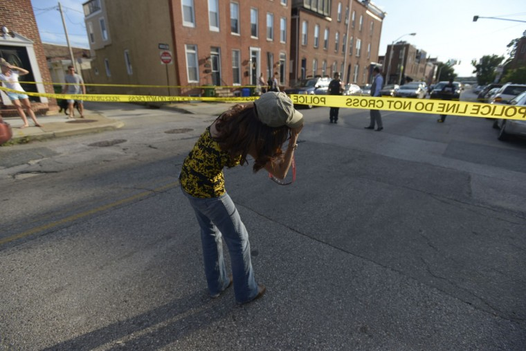"""Ybarra, 39, bends to get a shot of detectives at a shooting in Federal Hill on July 8, 2017. """"The majority of the time people are just pissed off that they can't get past the tape,"""" she said. (Christina Tkacik/Baltimore Sun)"""