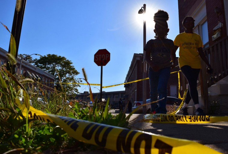 """""""A woman and child walk by the crime scene tape strewn around the place where a man was shot in the Eastern District in October 2016."""" (Photo and caption courtesy of Maggie Ybarra)"""