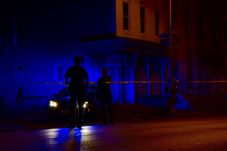 """""""A police officer explains to reporter Juliet Linderman that she can't cut around the crime scene tape at a mass shooting near the intersection of Greenmount Avenue and E. Preston Street. The shooting occurred on October 24, 2016, about 8:30 p.m."""" (Photo and caption courtesy of Maggie Ybarra)"""