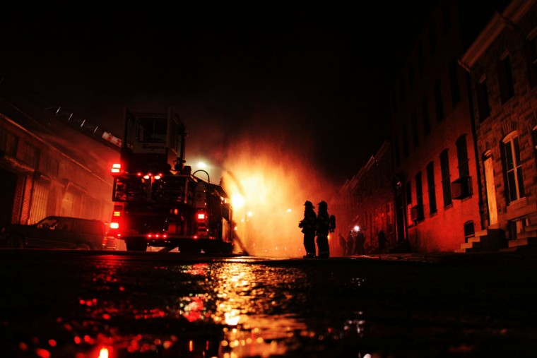 """""""Firefighters try to extinguish one of many blazes in the city on the night of the April 27, 2015, riot."""" (Photo and caption courtesy of Maggie Ybarra)"""