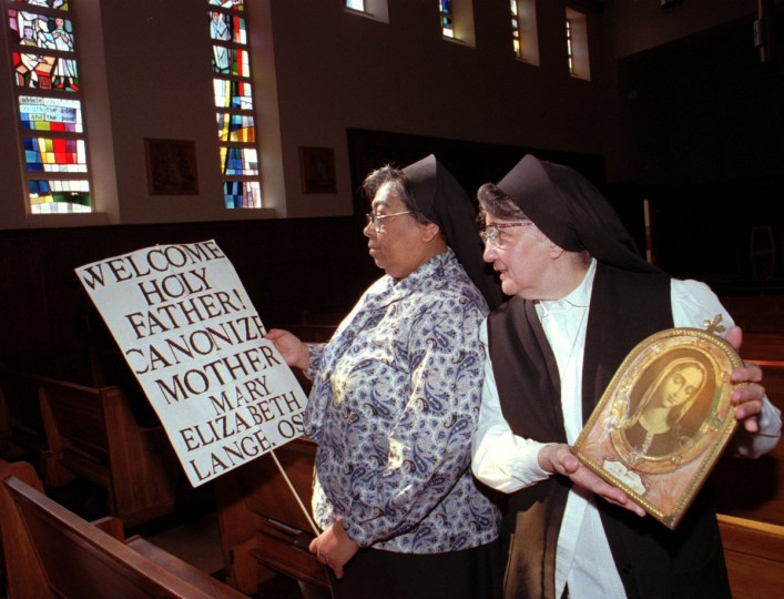 Baltimore,MD--10/19/95-At Our Lady of Mount Providence Convent's sanctuary, members of The Oblate Sisters of Providence, U.S.A. (the first black order of nuns) Sister Mary Reginald Gerdes,left and Sister Mary Reparata Clarke (archivist) will be cataloguing the order's artifacts with the help of a grant from The Baltimore County Historical Trust. The picket sign was used along the pope's parade route to remind the pontiff about the order's founder Sister Mary Elizabeth Lange and the order's desire to see that eventually she be canonized and the small picture, right, hung in Lange's room and is of Sainte Marie(Saint Mary) the blessed virgin. The French spelling reflects Sister Lange's knowledge of the language coming from the Isle of Hispaniola. (Jed Kirschbaum/Baltimore Sun)