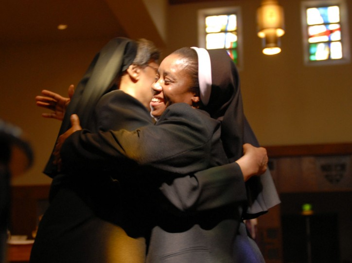 """CATONSVILLE, MD -- 3/25/09 -- MD OBLATES C KAWAJIRI -- Sister Mary Annette Beecham, Superior General of Oblate Sisters of Providence (LT), gives Sister Mary Anthonia Nwoga, a Nigerian-born woman in her 40s (RT) a hug after the """"Presentation of the Veil"""". Liturgy of the Eucharist and Rite of First Profession for Sister Anthonia Nwoga was held at the Oblate Sisters of Providence. This is a big deal for an order that has seen its numbers decline steadily for years as nuns die off and aren't replenished with new arrivals. The Oblate Sisters of Providence was founded in Baltimore in 1829 and is the first Roman Catholic religious order made up entirely of African American women. The taking of the black veil means Anthonia will go from """"novice"""" to """"professed sister,"""" and she'll then have five years to decide whether to make her """"final vows."""" The point is this is a big step toward becoming a lifelong member of the order. (CHIAKI KAWAJIRI/ Baltimore Examiner and Washington Examiner)"""