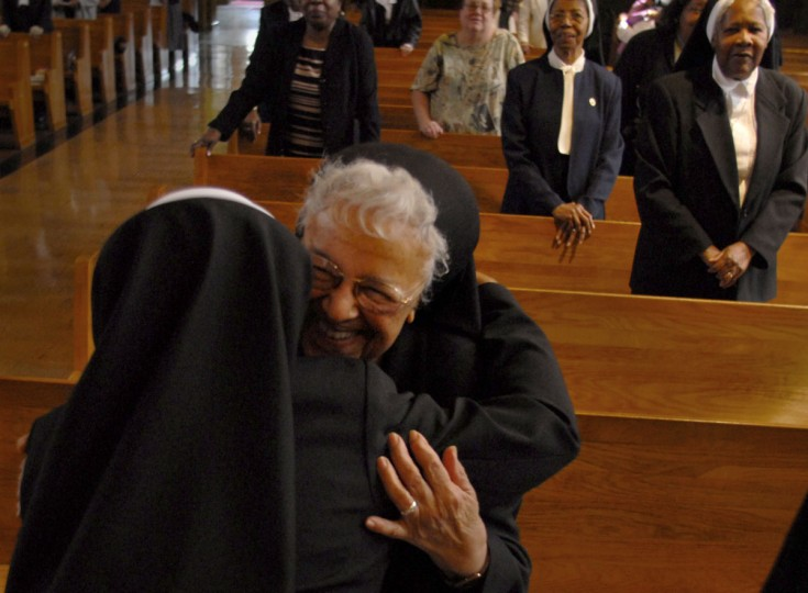 """CATONSVILLE, MD -- 3/25/09 -- Sister Mary Alice Chineworth, OSP, 91 (she will be 92 in July) (RT), gives Sister Mary Anthonia Nwoga, a Nigerian-born woman in her 40s (LT) a hug after the """"Presentation of the Veil"""". Liturgy of the Eucharist and Rite of First Profession for Sister Anthonia Nwoga was held at the Oblate Sisters of Providence. This is a big deal for an order that has seen its numbers decline steadily for years as nuns die off and aren't replenished with new arrivals. The Oblate Sisters of Providence was founded in Baltimore in 1829 and is the first Roman Catholic religious order made up entirely of African American women. The taking of the black veil means Anthonia will go from """"novice"""" to """"professed sister,"""" and she'll then have five years to decide whether to make her """"final vows."""" The point is this is a big step toward becoming a lifelong member of the order. (CHIAKI KAWAJIRI/Baltimore Sun)"""