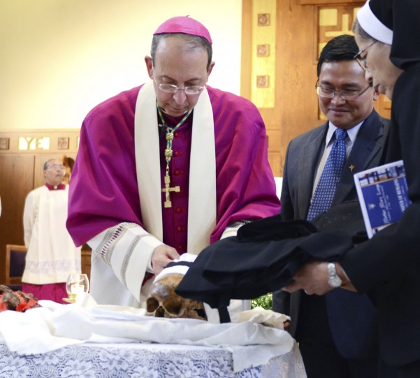 Baltimore Archbishop William E. Lori places the remains of Mother Mary Lange into a case before attendees of the ceremony are able to walk by and see them up close. Monday, June 3, 2013 in Arbutus. (Baltimore Sun archives)