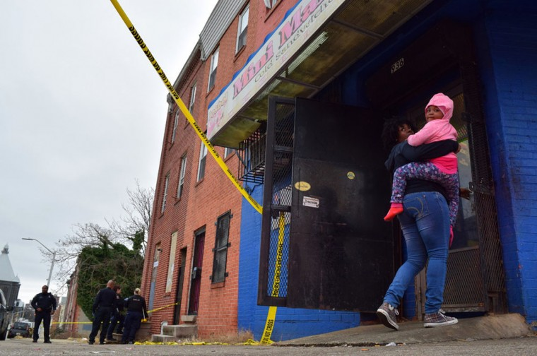 """""""A woman carries a child into the Mini Market while police investigate a shooting on E. Eager Street in January 2017."""" (Photo and caption courtesy of Maggie Ybarra)"""
