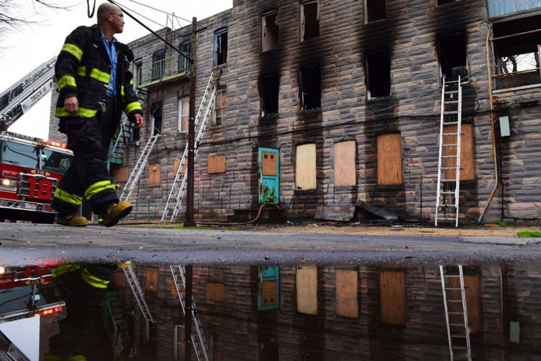 """""""A firefighter walks past a building that was destroyed by a fire and condemned in Marcy 2017."""" (Photo and caption courtesy of Maggie Ybarra)"""