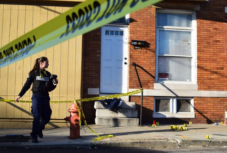 """""""A crime lab technician takes pictures of the corner of W. Fairmount Avenue where a man was shot on February 26, 2017."""" Photo and caption courtesy of Maggie Ybarra)"""