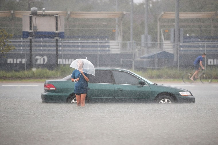 HOUSTON, TX - AUGUST 27: Mari Zertuche walks through a flooded parking lot on the campus of Rice University afer it was inundated with water from Hurricane Harvey on August 27, 2017 in Houston, Texas. Harvey, which made landfall north of Corpus Christi late Friday evening, is expected to dump upwards to 40 inches of rain in areas of Texas over the next couple of days. (Photo by Scott Olson/Getty Images)