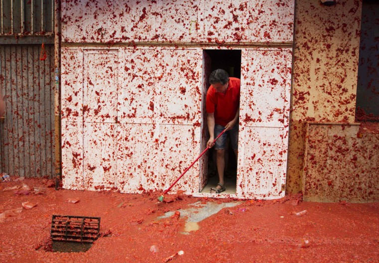 "A man cleans his front door during the annual ""Tomatina"" festival in the eastern town of Bunol, on August 30, 2017. The iconic fiesta -- which celebrates its 72nd anniversary and is billed at ""the world's biggest food fight"" -- has become a major draw for foreigners, in particular from Britain, Japan and the United States. (JAIME REINA/AFP/Getty Images)"