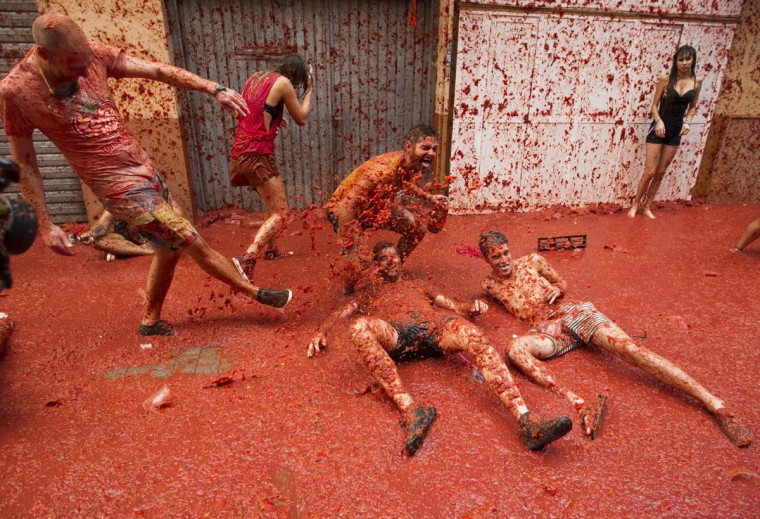"Revellers covered in tomato pulp take part in the annual ""Tomatina"" festival in the eastern town of Bunol, on August 30, 2017. The iconic fiesta -- which celebrates its 72nd anniversary and is billed at ""the world's biggest food fight"" -- has become a major draw for foreigners, in particular from Britain, Japan and the United States. (JAIME REINA/AFP/Getty Images)"