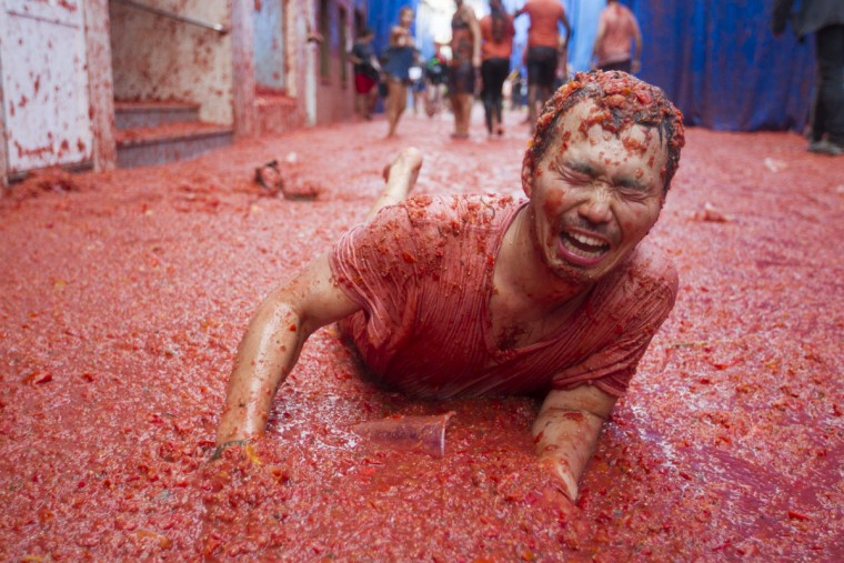 "A reveller covered in tomato pulp takes part in the annual ""Tomatina"" festival in the eastern town of Bunol, on August 30, 2017. The iconic fiesta -- which celebrates its 72nd anniversary and is billed at ""the world's biggest food fight"" -- has become a major draw for foreigners, in particular from Britain, Japan and the United States. (JAIME REINA/AFP/Getty Images)"