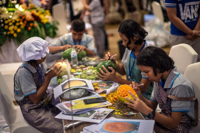 Thai children carve elaborate designs into fruit and vegetables during a fruit and vegetable carving competition in Bangkok on August 4, 2017. It is a royal tradition that has proved bountiful through the ages and one that Thailand's fruit carvers are determined to keep alive -- even as young people peel away from the unique art form. (ROBERTO SCHMIDT/AFP/Getty Images)
