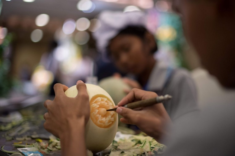 A Thai girl carves floral patterns into a melon during a fruit and vegetable carving competition in Bangkok on August 4, 2017. It is a royal tradition that has proved bountiful through the ages and one that Thailand's fruit carvers are determined to keep alive -- even as young people peel away from the unique art form. (ROBERTO SCHMIDT/AFP/Getty Images)