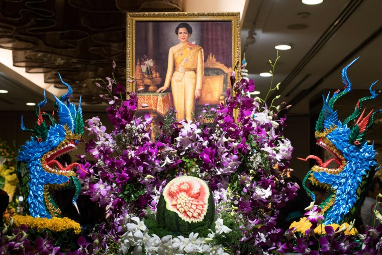 A painting depicting Thailand's Queen Sirikit adorns an elaborate fruit and vegetable decoration during a fruit and vegetable carving competition in Bangkok on August 4, 2017. It is a royal tradition that has proved bountiful through the ages and one that Thailand's fruit carvers are determined to keep alive -- even as young people peel away from the unique art form. (ROBERTO SCHMIDT/AFP/Getty Image)