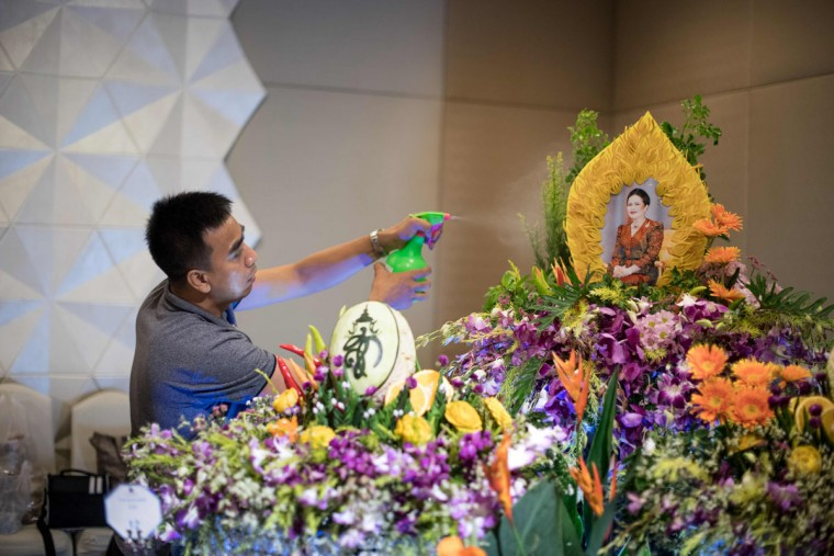 A worker sprays water on an elaborate fruit and vegetable decoration adorned with the photograph of Thailand's Queen Sirikit during a fruit and vegetable carving competition in Bangkok on August 4, 2017. It is a royal tradition that has proved bountiful through the ages and one that Thailand's fruit carvers are determined to keep alive -- even as young people peel away from the unique art form. (ROBERTO SCHMIDT/AFP/Getty Images)